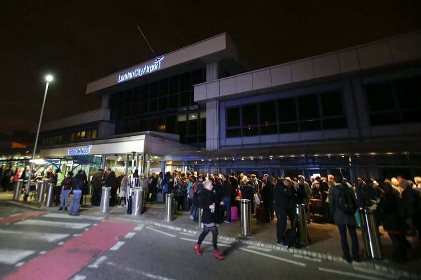 Passengers queue outside the entrance to London's City Airport on Oct 21, 2016 after an evacuation.