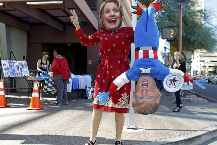 A man wears a mask depicting Clinton while holding a doll depicting her rival, Donald Trump, in Phoenix, Arizona Oct 20, 2016.