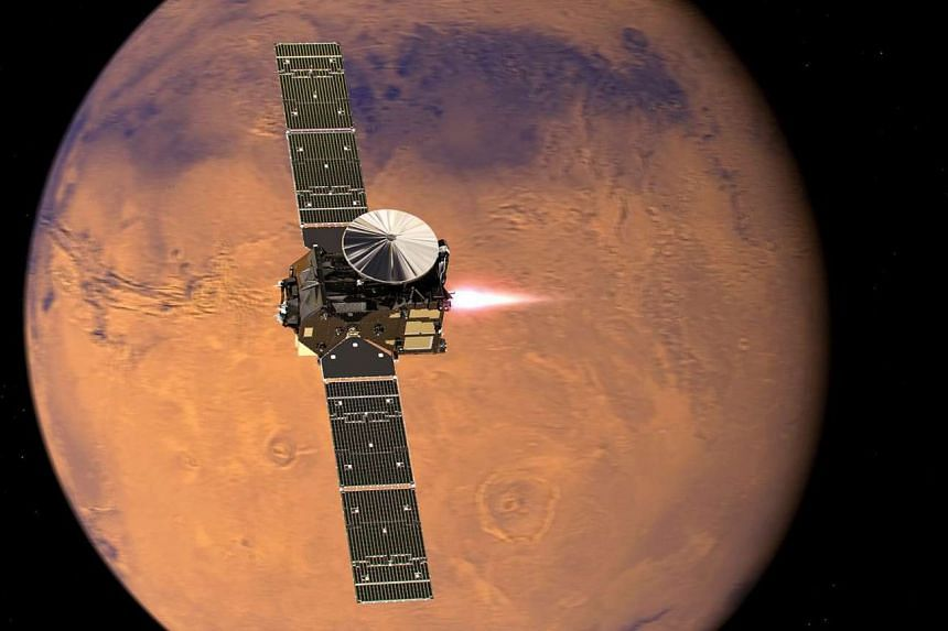 An artist's impression shows the ExoMars 2016 Trace Gas Orbiter, with its thrusters firing, beginning its entry into Mars orbit.
