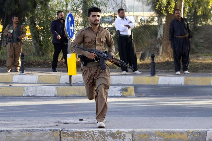 A member of peshmerga forces runs at the site of an attack by ISIS militants in Kirkuk, Iraq, Oct 21, 2016.