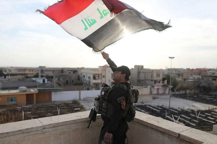 An Iraqi special forces soldiers waves an Iraqi flag from top of a church damaged by Islamic States fighters in Bartella.
