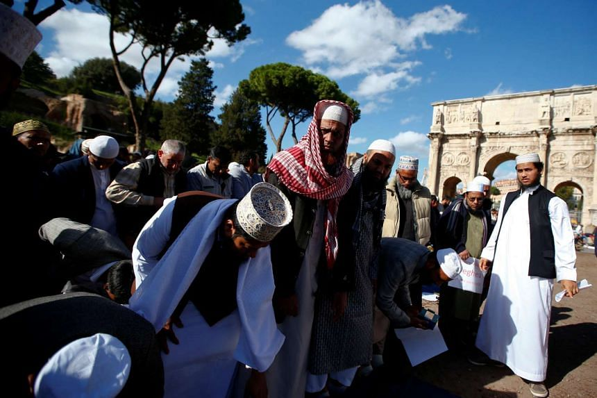 Muslims hold Friday prayers in front of the Colosseum in Rome, to protest against the closure of unlicensed mosques.