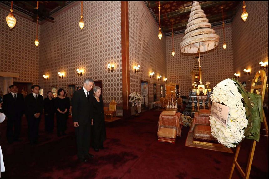 PM Lee and Mrs Lee paying their respects to the late King Bhumibol Adulyadej at the Grand Palace in Bangkok yesterday. PM Lee signed a condolence book and laid a wreath at the palace.