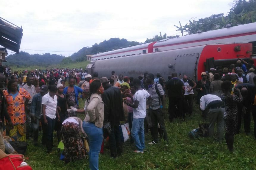 People crowd around the derailed train which was travelling between Cameroon's capital Yaounde and the port city of Douala .