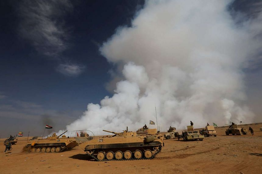 The toxic cloud is seen as the Iraqi army gathers after liberating a village from ISIS militants on Oct 21, 2016.