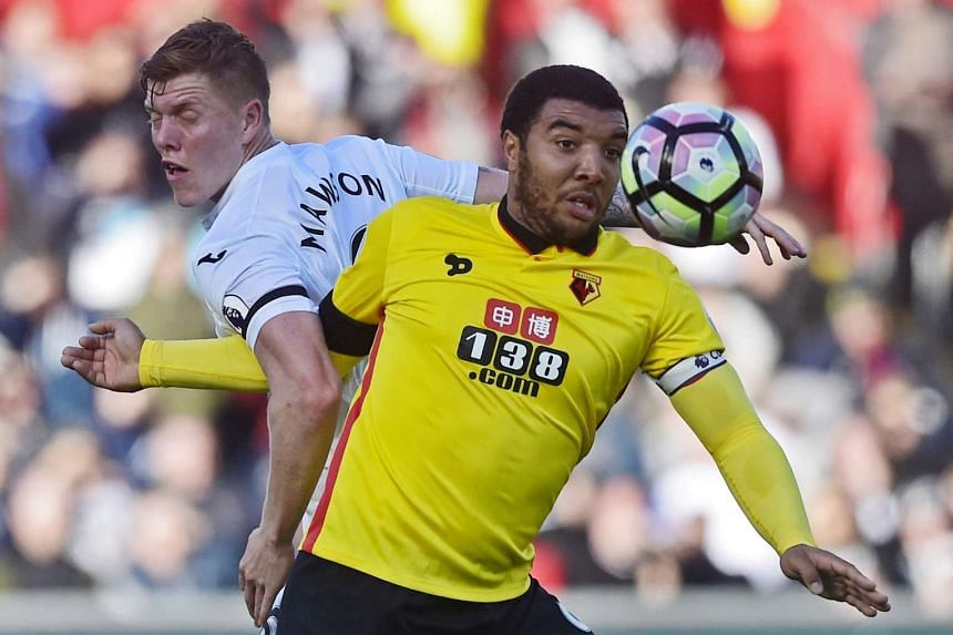 Swansea City's Alfie Mawson in action with Watford's Troy Deeney.