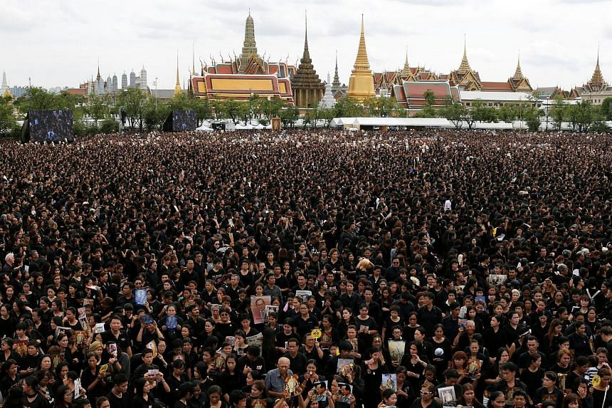 Yesterday, Thai citizens in mourning garb formed a sea of black, filling the large grassy field outside the royal compound and surrounding roads. They sang a royal anthem alongside a 100-piece orchestra and professional choir.