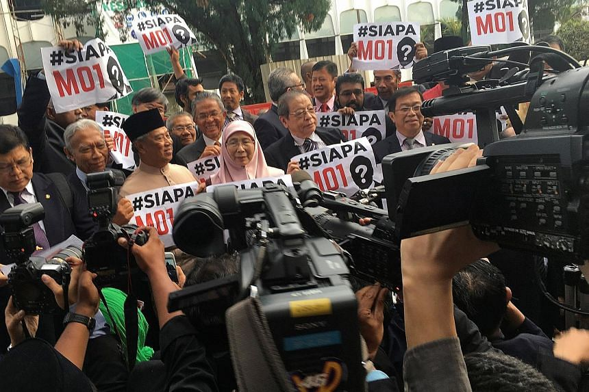 """Malaysian opposition MPs holding up placards asking """"Who is MO1 (Malaysian Official 1)?"""" after staging a walkout in protest in Parliament while Prime Minister Najib Razak was tabling the country's next Budget in Kuala Lumpur on Friday. Datuk Seri Naj"""