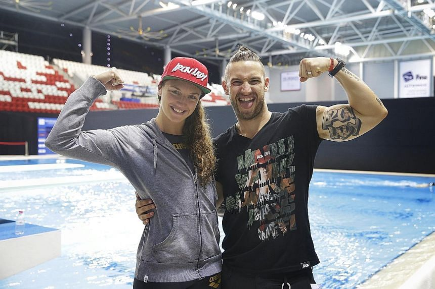 Triple Olympic champion Katinka Hosszu and Shane Tusup flexing their biceps in a signature pose at the OCBC Aquatic Centre yesterday. He makes no excuses for his abrasive behaviour.