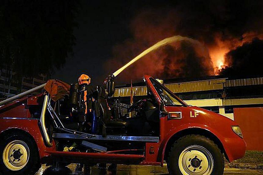 SCDF firefighters working to put out the blaze in Kallang Way on Sept 6, 2012. The High Court found that the blaze started on the premises of Grace Electrical Engineering and ruled that the company is liable for the fire.