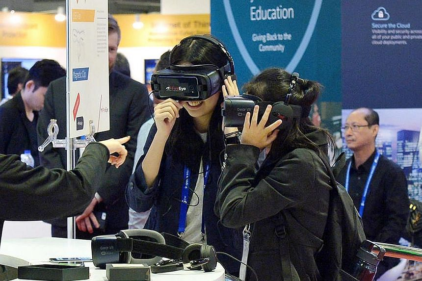 Visitors trying out virtual reality goggles at the FireEye booth (left) and a Cisco exhibition worker (above) during the Singapore International Cyber Week at Suntec Convention and Exhibition Centre earlier this month. Studies have found that cyber a