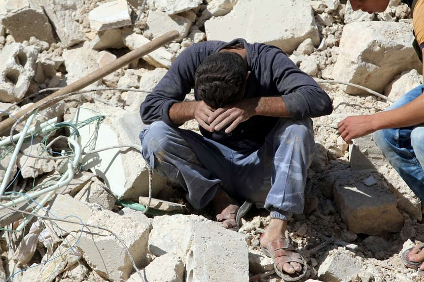 A man reacts on the rubble of damaged buildings after losing relatives to an airstrike in the besieged rebel-held al-Qaterji neighbourhood of Aleppo, Syria, Oct 11, 2016.