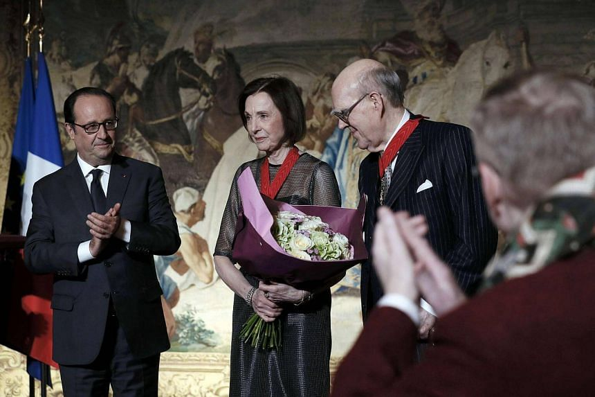 French President Francois Hollande applauds as he stands with American collectors Marlene and Spencer Hays after they were named Commandeur de la Legion d'Honneur at a ceremony in Paris.