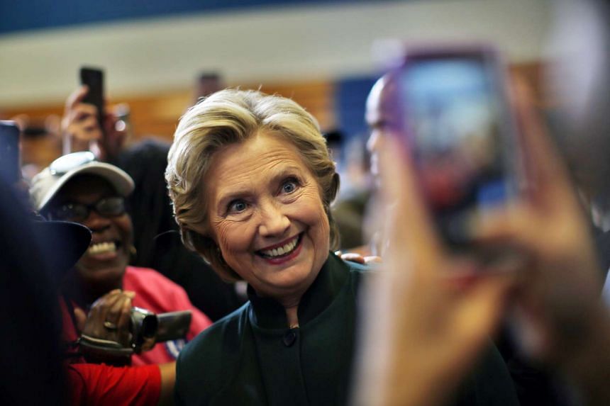 Clinton poses for a picture during a campaign event in Cleveland, Ohio, Oct 21, 2016.