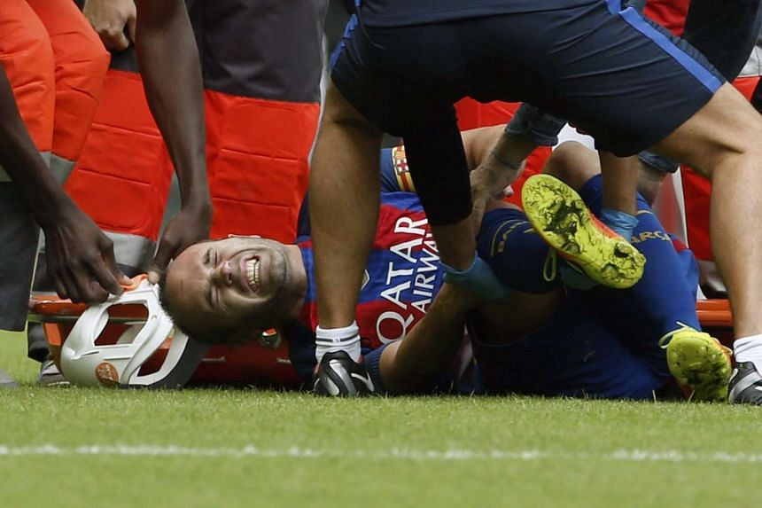Barcelona's midfielder Andres Iniesta reacts in pain after picking up an injury during the match against Valencia.