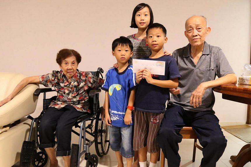 Siblings Trinity Ong, 10, Noah, 8, and Casper, 5, handing over a carefully decorated envelope containing $500 - most of the money from their piggy banks - to Mr Neo Chwee Eng, 81, a yong tau foo seller whose stall was destroyed in a fire.