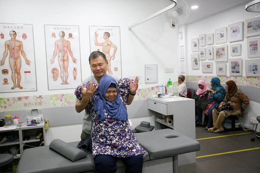 Traditional Chinese Medicine (TCM) physician Lam Kean Lung treating Madam Kamisah Suria, 62, at a Sian Chay Medical Institution clinic in Geylang.