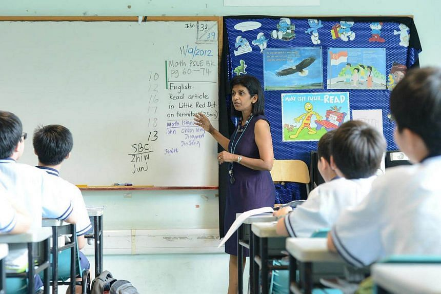 A teacher pointing out the homework listed on the whiteboard to her class at Jing Shan Primary School.