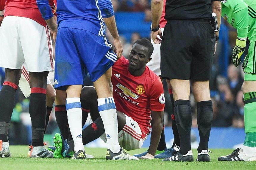 Manchester United's Eric Bailly being helped to his feet after suffering an injury.