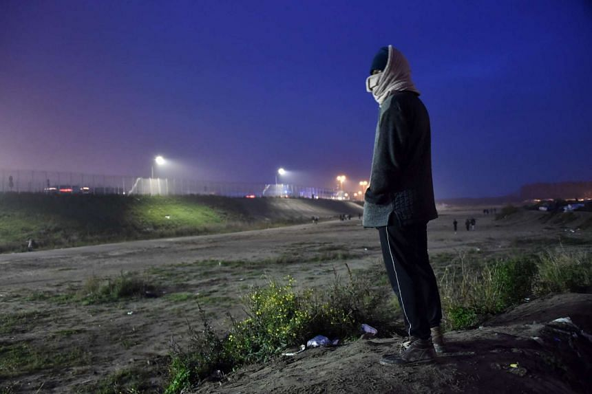 A migrant looks at the Calais migrant camp before leaving on Oct 24, 2016.