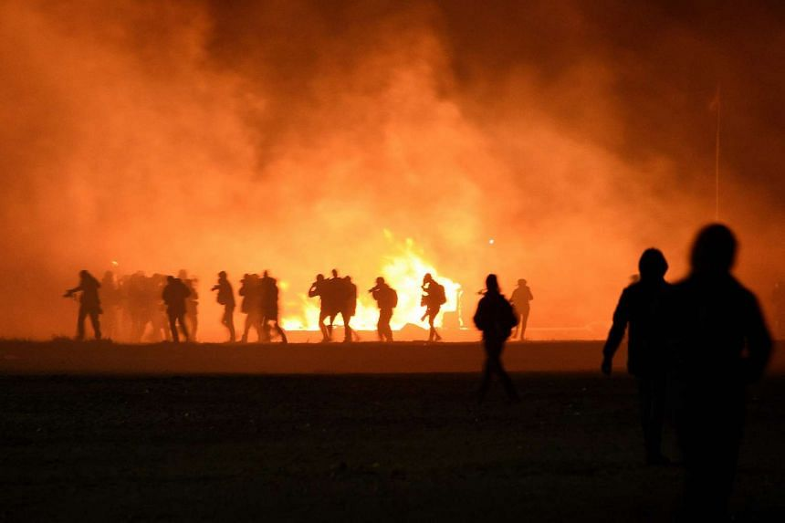 Smoke billows as migrants start a fire during clashes with police at the migrant camp in Calais on Oct 23, 2016.
