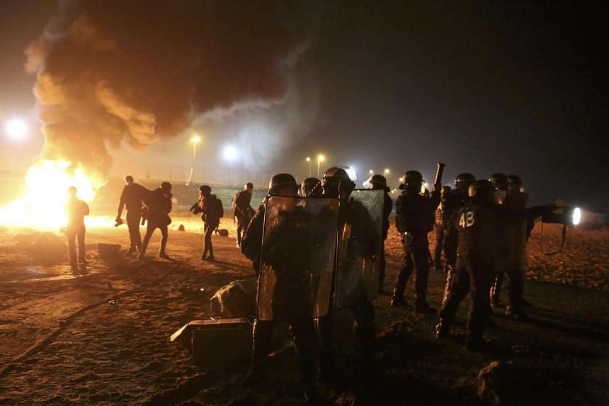 French riot police intervene after migrants set garbage bins on fire in the Calais migrant camp in France on Oct 24, 2016.