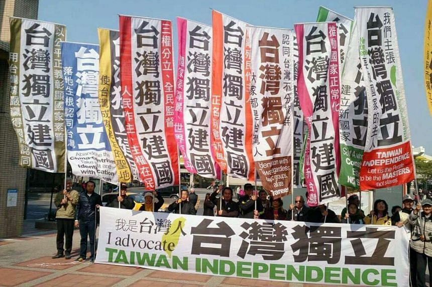 """Taiwan Independence Flag Team members displaying flags with the slogan """"Taiwan Independence and Establish a Nation"""" and a placard """"I Am Taiwanese, Taiwan Independence"""" on Oct 17, 2016."""