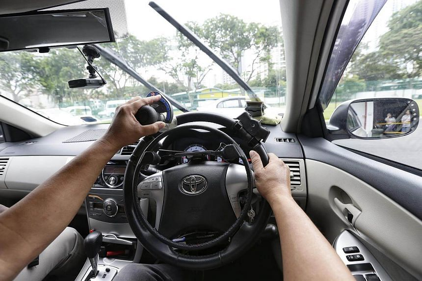 Mr Simon Ching, 50-year-old transport manager of Handicaps Welfare Association (HWA), demonstrating the use of the Infra-Red Tele-Command device (in left hand, controlling the windscreen wiper) with Over-Ring Accelerator and mechanical brake speciall