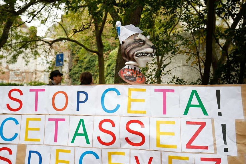 A placard reads 'Stop CETA - it's enough' during an anti-CETA protest in front the Walloon parliament in Namur, Belgium on October 21, 2016, during a meeting on CETA (EU-Canada Comprehensive Economic and Trade Agreement).