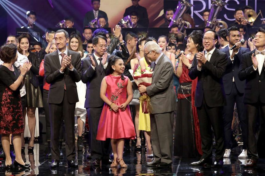 Jadyn Lavinia Cai (in red), 12, giving a bouquet of flowers to President Tony Tan. She performed with singer Sezairi Sezali during at the President Star Charity.