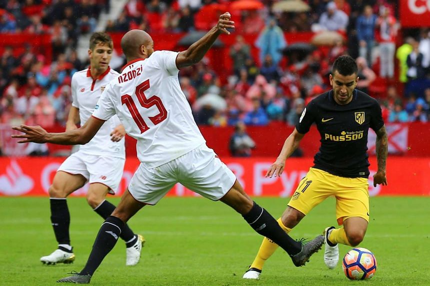 Sevilla's Steven N'Zonzi and Atletico Madrid's Angel Correa in action.