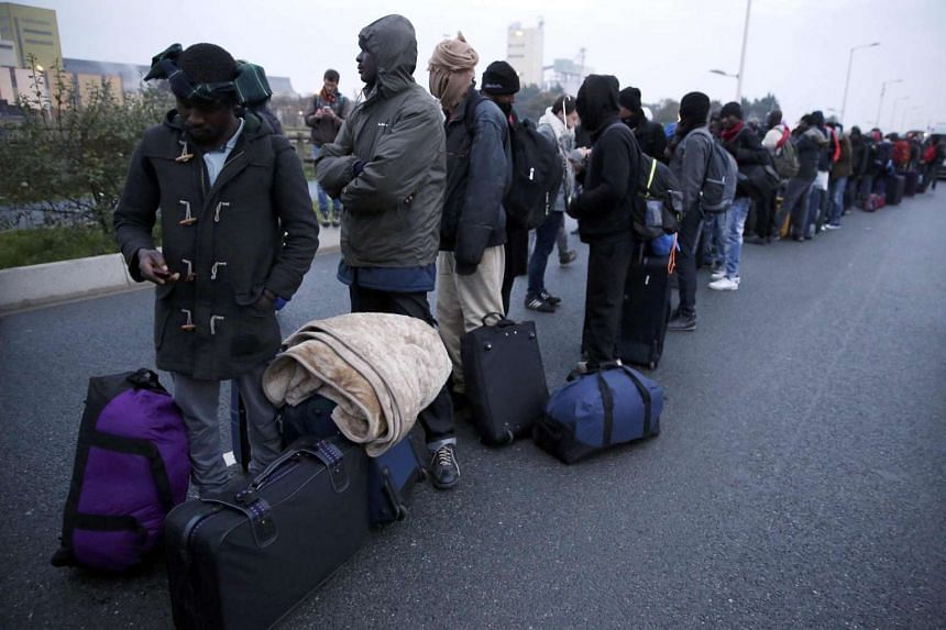 Migrants with their belongings queue at the start of their evacuation and transfer to reception centers in France on Oct 24, 2016.