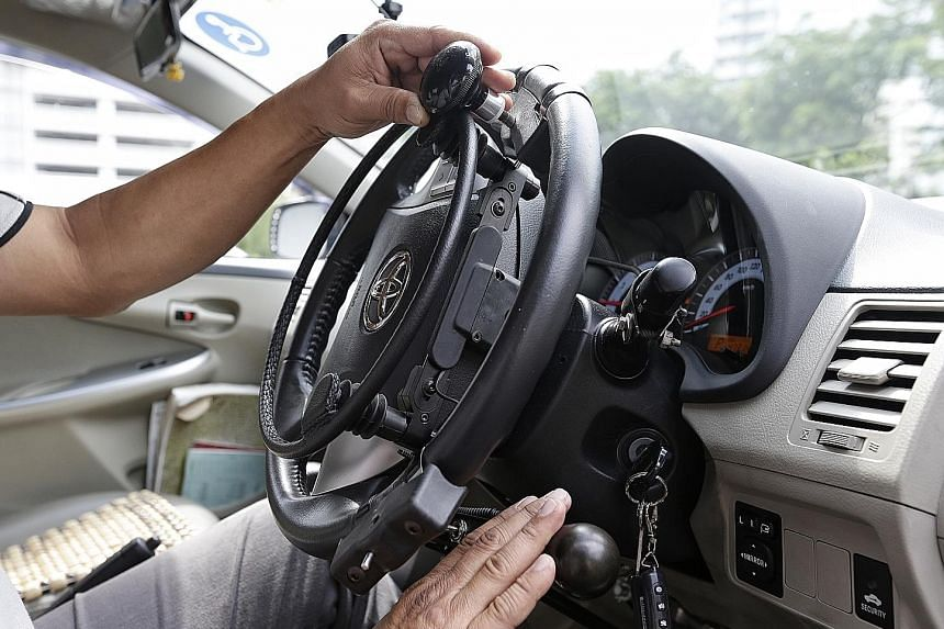 The Handicaps Welfare Association's Mr Ching demonstrating the use of an over-ring accelerator (in his left hand) and a mechanical brake (in his right hand). Such devices help drivers overcome their disabilities.