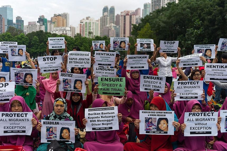 Migrant workers holding a vigil for fellow Indonesians Sumarti Ningsih and Seneng Mujiasih at Victoria Park in Hong Kong yesterday. The two women were stabbed to death in the luxury flat of Briton Rurik George Caton Jutting in November 2014. The form