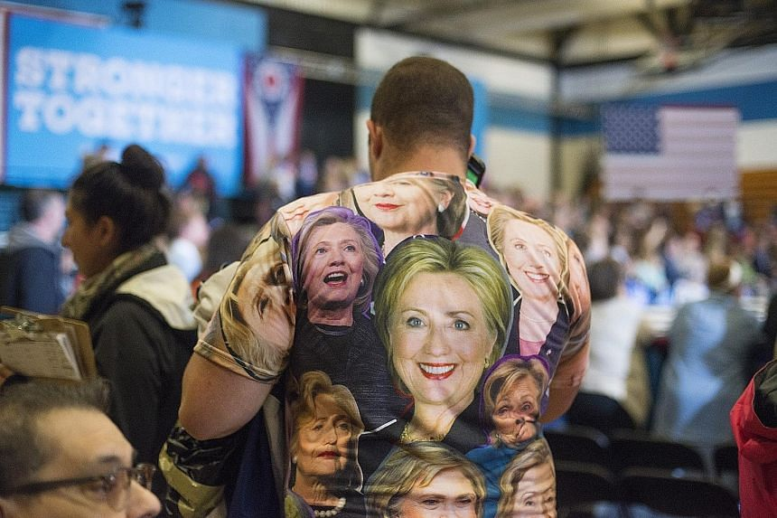 A Clinton supporter at a rally in Cleveland, Ohio, last Friday. Mrs Clinton and Mr Trump are currently tied in the battleground state, according to polls. Mrs Clinton at a campaign event with her running mate Tim Kaine in Philadelphia on Saturday.