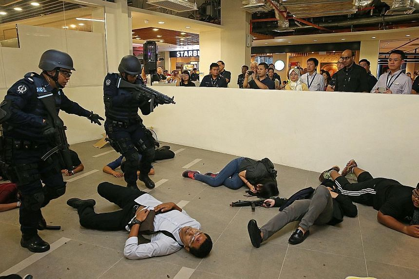 Police Emergency Response Team officers carrying out an anti-terrorism exercise in the food and beverage area of Ng Teng Fong General Hospital yesterday evening as DPM Tharman looks on.