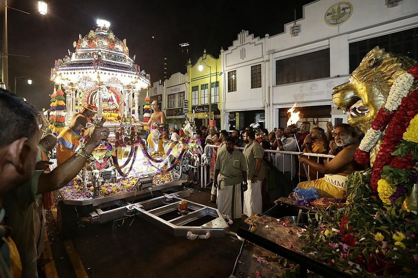 Devotees flanking a chariot as it arrives at the entrance of Singapore's oldest Hindu temple, the Sri Mariamman Temple in South Bridge Road, at around 1.05am yesterday. It had made its way to the temple in Chinatown from the Sri Srinivasa Perumal Tem