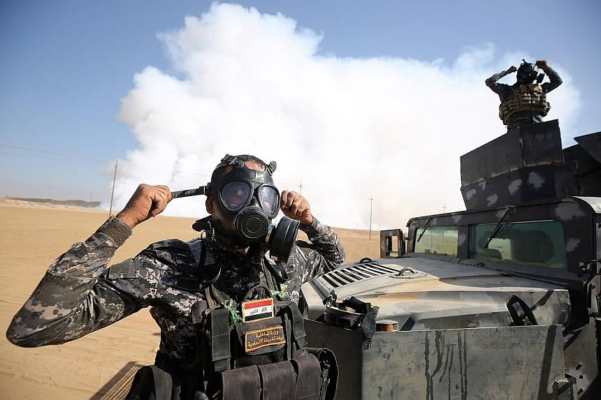 Iraqi forces wearing gas masks after fighters from the Islamic State in Iraq and Syria torched a sulphur factory about 30km south of Mosul on Saturday. The move was done in an effort to halt the offensive to recapture the city.