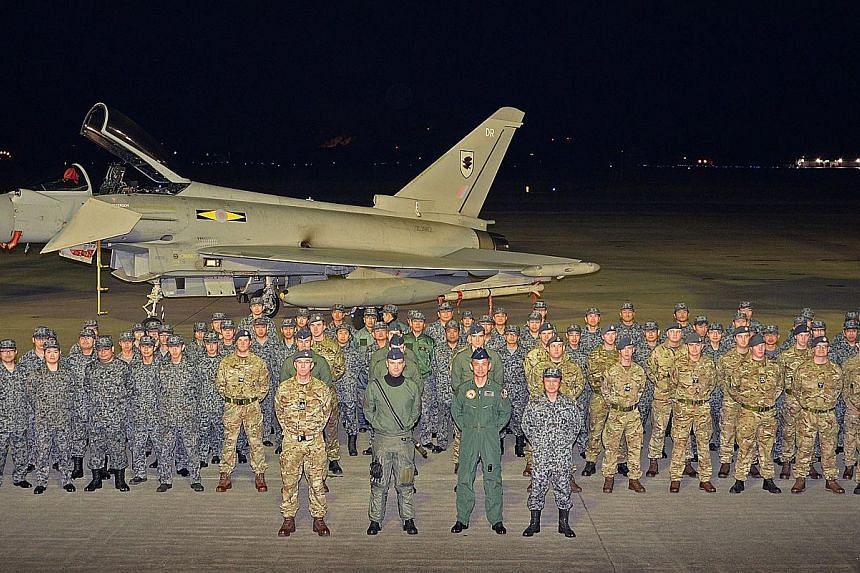 Japanese and British air force personnel in front of a Typhoon jet at Misawa Air Base. The pilots are competing and training together in an exercise dubbed Guardian North 16, which began yesterday.