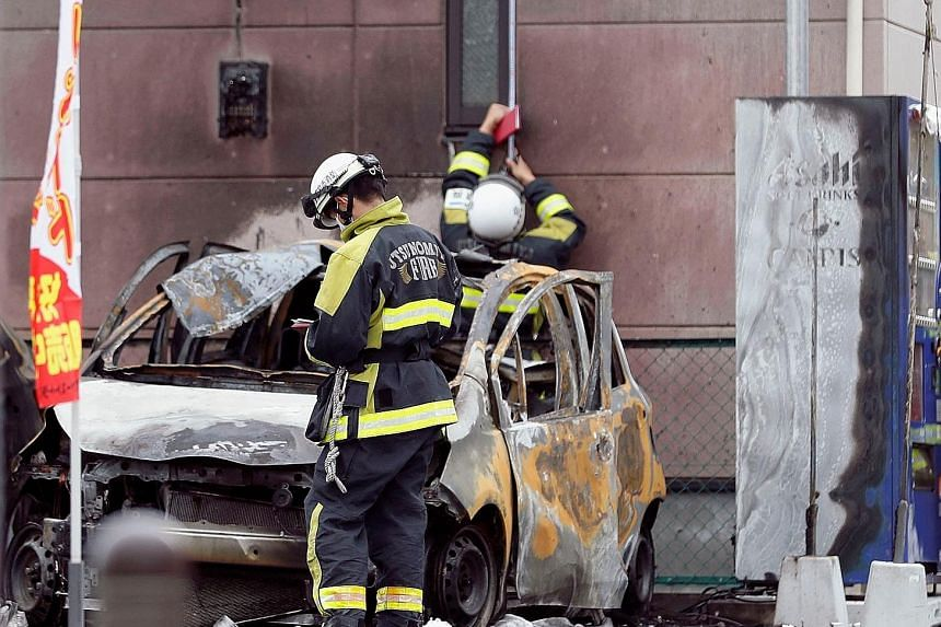 Firefighters investigating one of the burnt-out cars found after the explosions in Utsunomiya yesterday. A retired soldier killed himself in one of the explosions, which also injured two other men and a teenage boy.