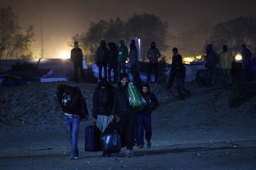 Migrants leave the 'Jungle' migrant camp in Calais, northern France, on Oct 23, 2016, on the eve of the camp's planned evacuation.