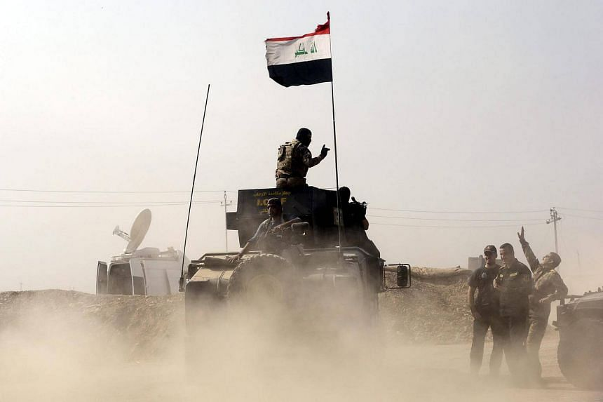 An armoured vehicle carrying soldiers of the Iraqi Army sets off towards the former ISIS-held town of Bartila.