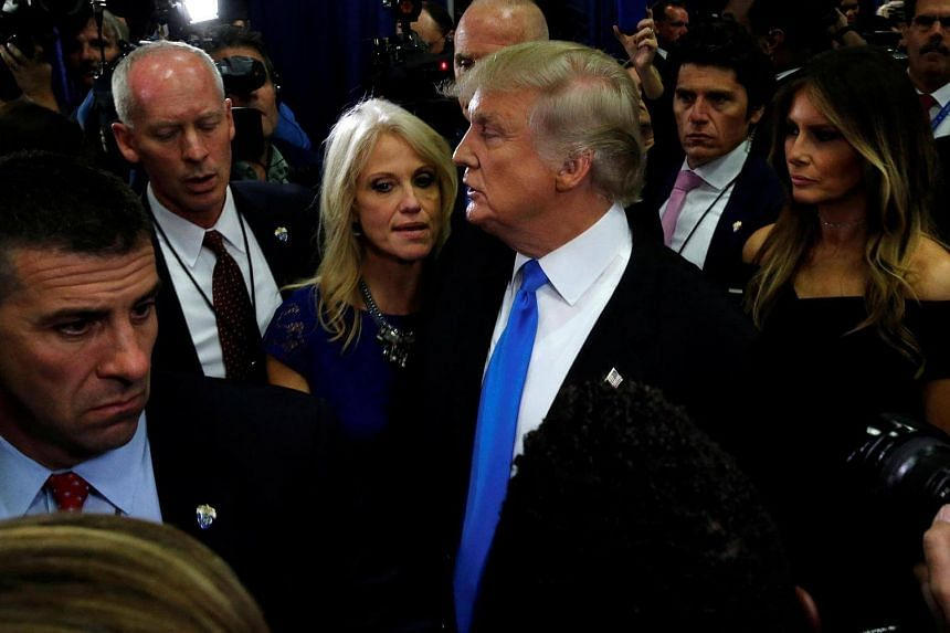 Mr Donald Trump speaks to campaign manager Kellyanne Conway in the spin room after the first US presidential debate.