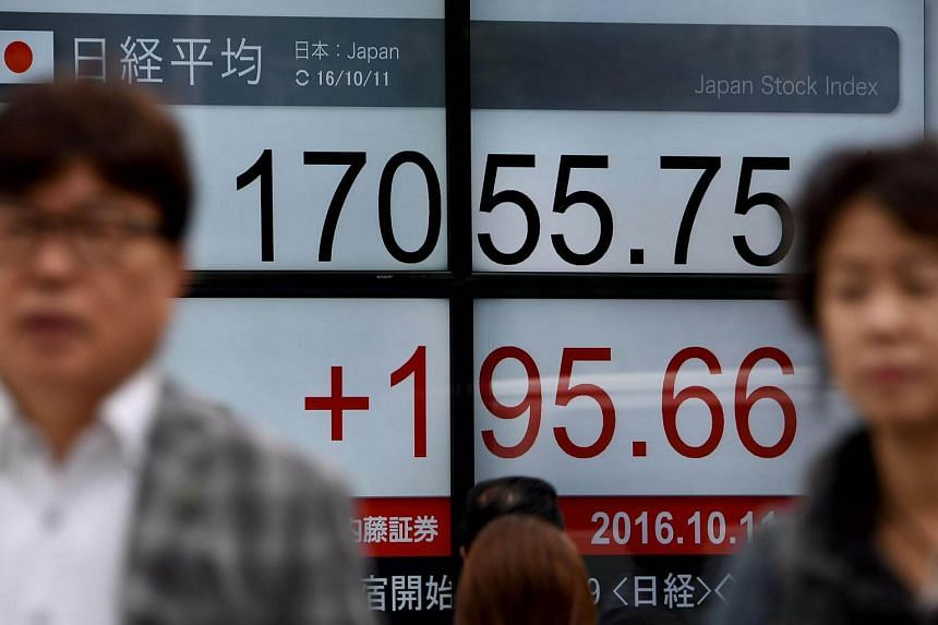 People walk past a board flashing the Nikkei key index in front of a securities firm in Tokyo.