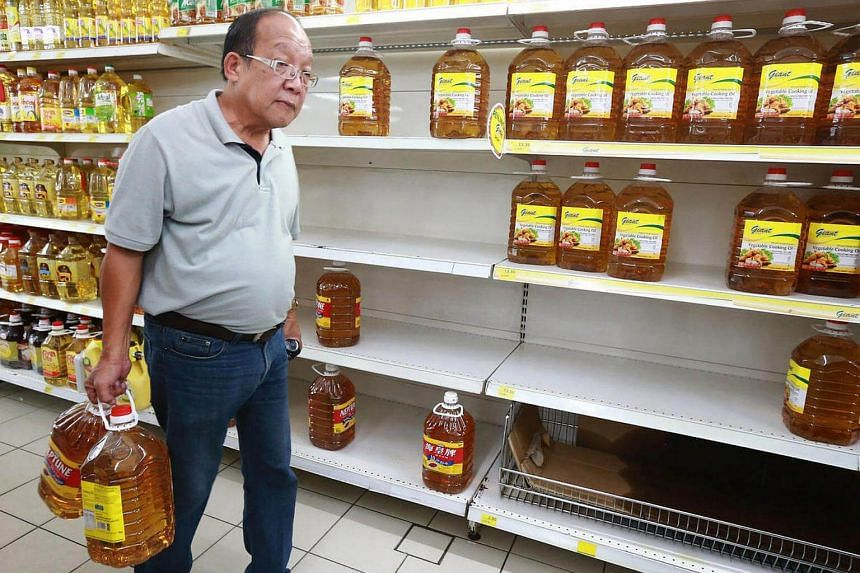 An elderly man carrying two bottles of oil at a supermarket in Malaysia.