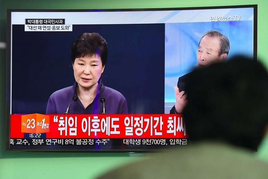 People watch a television screen showing South Korean President Park Geun Hye making a public apology, at a train station in Seoul on Oct 25, 2016.