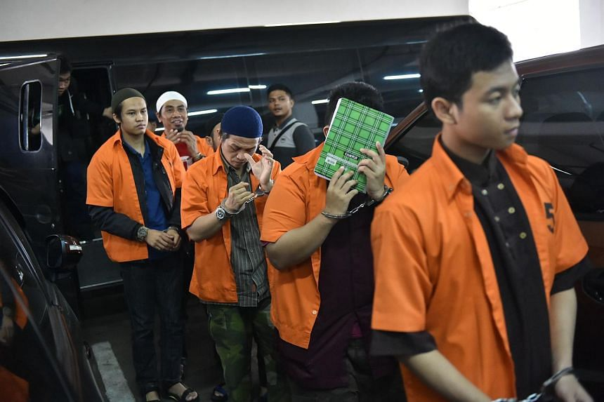 Ali Makhmudin (in blue cap), an ISIS supporter, along with other terror suspects arriving at a court in Jakarta on Oct 25, 2016.