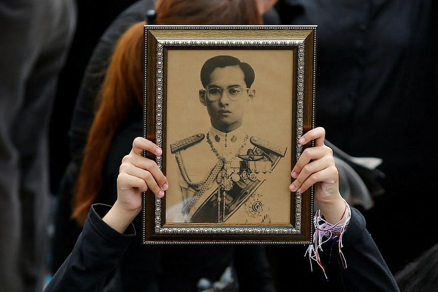 A Thai mourner holds a portrait of the late King Bhumibol Adulyadej outside the Grand Palace in Bangkok on Oct 22, 2016. PHOTO: REUTERS