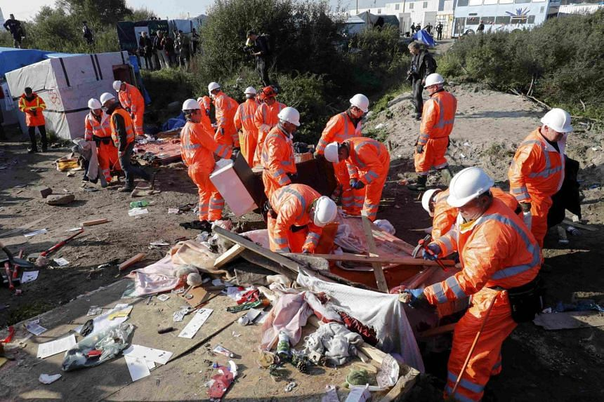 """Workmen tearing down a makeshift shelter on the second day the evacuation of migrants and their transfer to reception centers in France, as part of the dismantlement of the camp called the """"Jungle"""" in Calais, France, on October 25, 2016."""