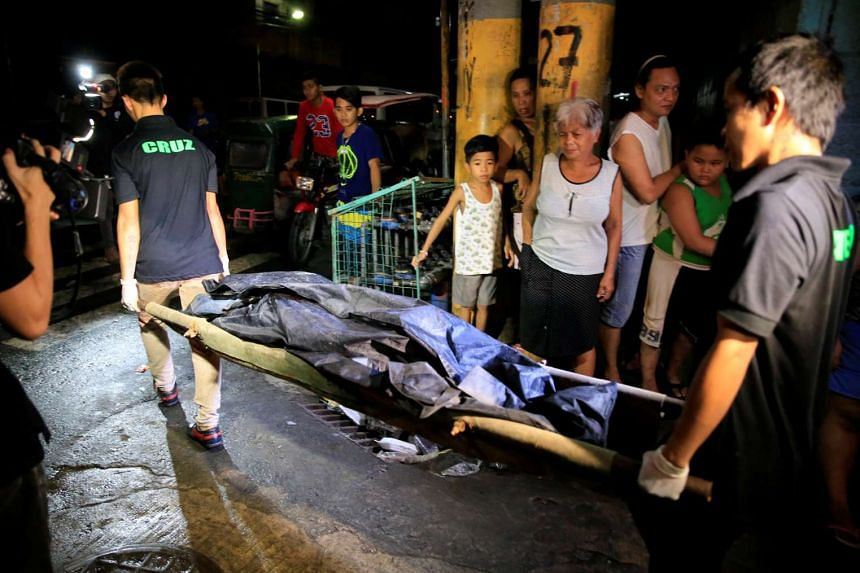 Funeral workers carry the body of a man who died after a gunfight with local police inside his house during a drug bust in metro Manila on Oct 19, 2016.